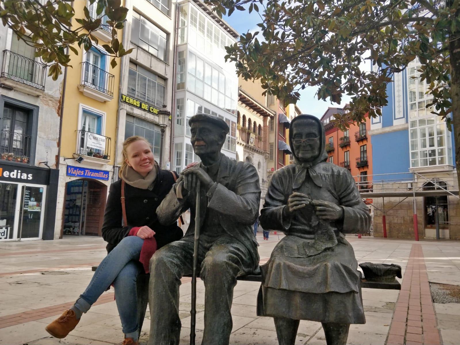 Persona sentada junto a dos estatuas