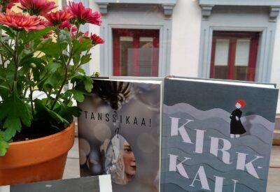 dos libros finlandeses junto a una planta