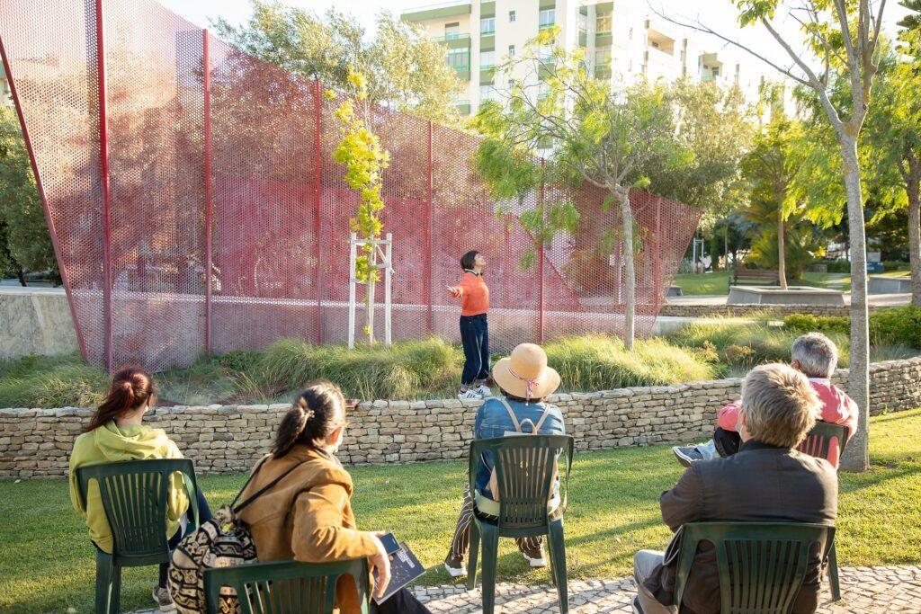 nainen puhuu yleisölle puistossa